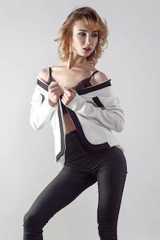 Modelka pozuje w białej kurtce na szarym tle
