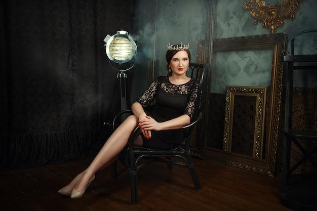 Modelka pozuje w ciemnym studio jako królowa