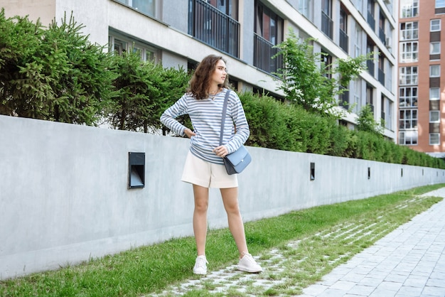 Modelka pozuje w nowej kolekcji ubrań na zewnątrz w mieście na tle domów