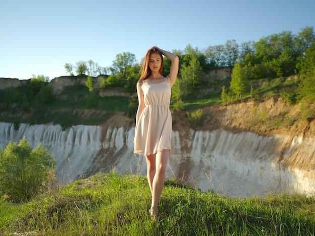 Modelka pozuje w słoneczny dzień z pięknym słonecznym krajobrazem wokół niej. młoda kobieta stojąca przy klifie z ładnym widokiem za plecami. atrakcyjna dziewczyna w białej sukni, pozowanie na zewnątrz.