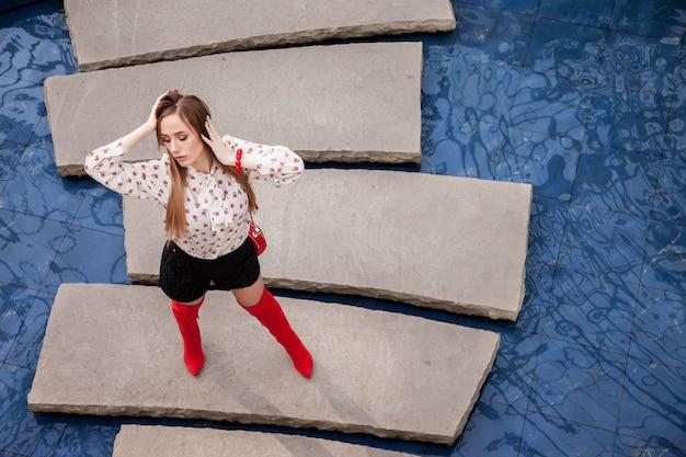 Modelka reklamująca sklep z modą lub centrum handlowe. stylowa brunetka pozuje profesjonalnie do kamery na wyspie na błękitnej wodzie. pojęcie piękna; styl; sklep lub podróż. skopiuj miejsce