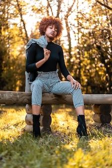 Modelka siedząca na siedzeniu w lesie z amerykaninem na ramieniu