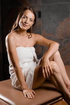 Modelka siedzi na stole do masażu w spa. piękno portret kobiety z idealną skórą.