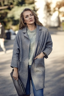 Modelka sobie podarte dżinsy chłopaka, kurtkę i trampki, pozowanie na ulicy miasta. modny strój miejski