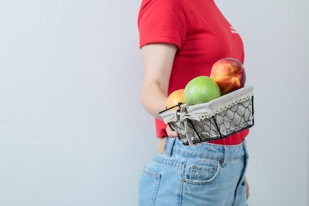Modelka trzyma kosz z owocami