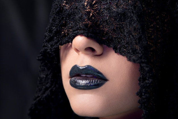 Modelka ubrana w gotycki makijaż z czarnym koronkowym szalikiem