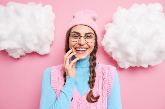 Modelka uśmiecha się szeroko wyraża szczęśliwe emocje ma białe zęby nosi codzienne ubrania okrągłe przezroczyste okulary izolowane na różowo