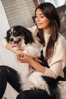 Modelka w białej koszuli z czarnym białym psem