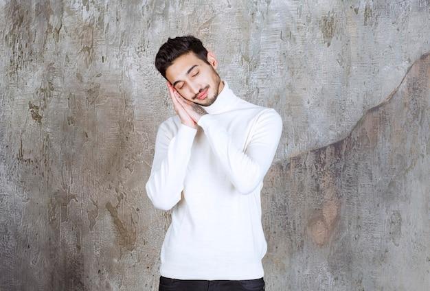 Modelka w białym swetrze stojąca na betonowej ścianie i wygląda na śpiącą lub zmęczoną.