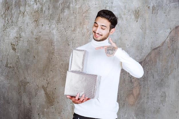 Modelka w białym swetrze trzyma dwa srebrne pudełka na prezenty.