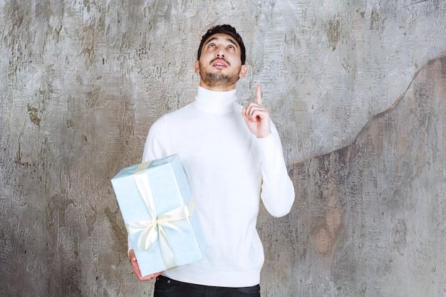 Modelka w białym swetrze trzyma niebieskie pudełko owinięte białą wstążką i pokazuje coś powyżej.
