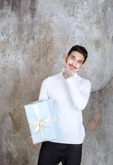 Modelka w białym swetrze trzyma niebieskie pudełko owinięte białą wstążką i wygląda na zamyśloną lub niezdecydowaną.