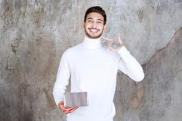 Modelka w białym swetrze trzyma srebrne pudełko i wskazuje na kogoś lub coś w pobliżu.