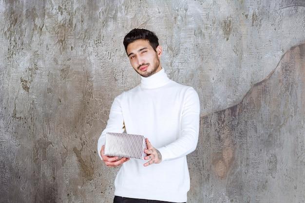 Modelka w białym swetrze trzyma srebrne pudełko.