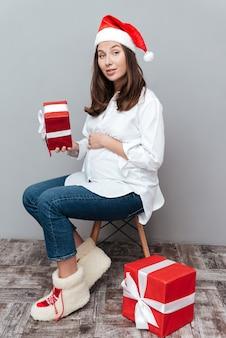 Modelka w ciąży z prezentem siedząca na krześle