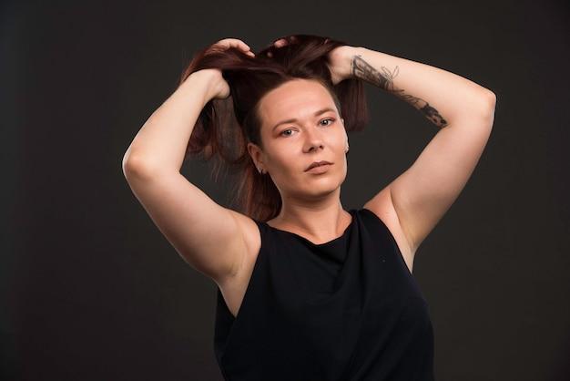 Modelka w czarnej koszuli promującej fryzurę.
