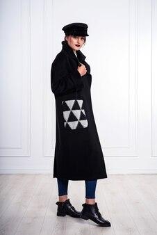 Modelka w czarnym długim płaszczu, w czapce. trójkątny wzór na kieszeni