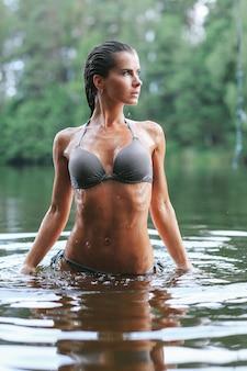 Modelka w czarnym stroju kąpielowym w jeziorze