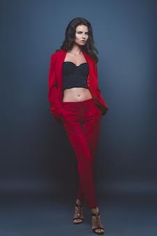 Modelka w czerwonym kolorze. młoda kobieta pozuje w czerwonym kolorze na szaro