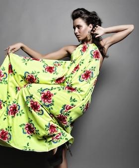 Modelka w jasnej sukience na szarym tle