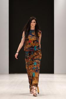 Modelka w jedwabnej sukni z etnicznym ornamentem chodzącym na podium podczas pokazu tygodnia mody.