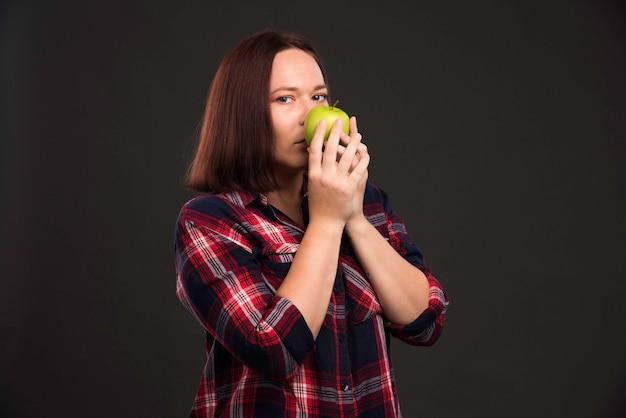 Modelka w jesienno-zimowej kolekcji strojów trzyma zielone jabłko i wącha je.