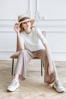 Modelka w kapeluszu i stylowe ubrania pozuje siedząc na krześle w studio