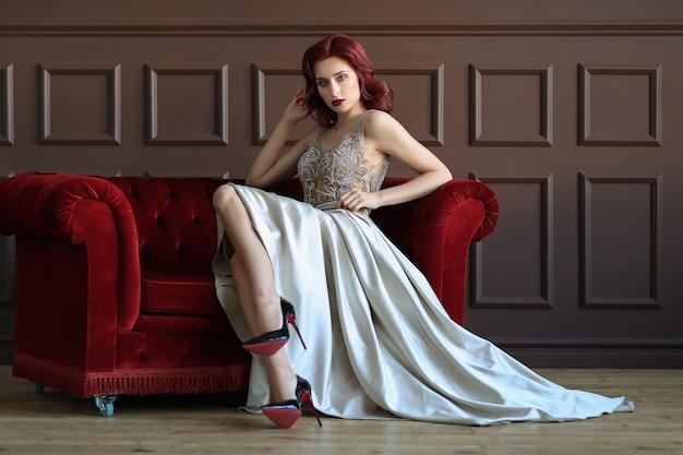 Modelka w niebieskiej eleganckiej sukni siedzi na czerwonej kanapie