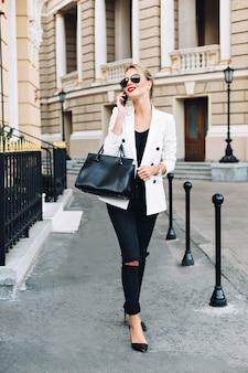 Modelka w okularach przeciwsłonecznych idzie na ulicy na piętach. mówi przez telefon i uśmiecha się na bok.