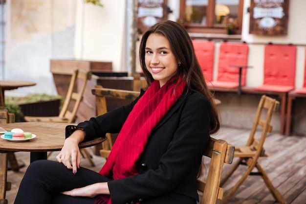 Modelka w płaszczu siedzi na krześle w kawiarni patrząc w kamerę
