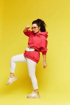 Modelka w różowej koszulce, modnych okularach przeciwsłonecznych iz torbą na pasku na żółtym tle