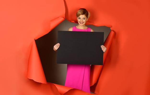 Modelka w różowej sukience wyłaniająca się z podartego papieru modna kobieta z idealnym makijażem czerwonymi ustami
