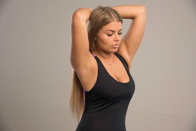Modelka w sportowym biustonoszu kładzie ręce za głowę.