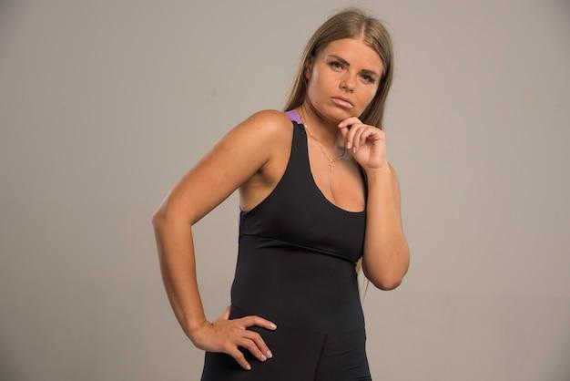 Modelka w sportowym staniku wygląda kusząco z rękami na brodzie.
