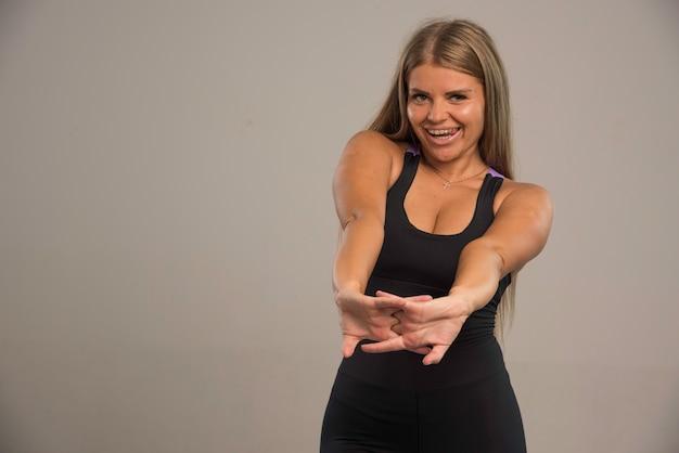 Modelka w staniku sportowym, rozciąganie ramion przed treningiem i wygląda pozytywnie.