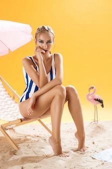 Modelka w strojach kąpielowych z ręką na twarzy wygląda prosto