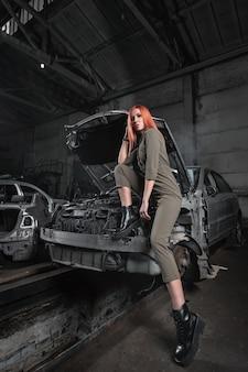 Modelka w stylowych ubraniach siedzi na otwartej masce w zdemontowanym samochodzie w garażu.