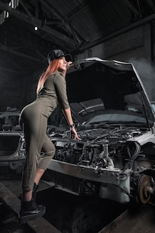 Modelka w stylowym ubraniu stojąca na otwartej masce w zdemontowanym samochodzie w garażu.