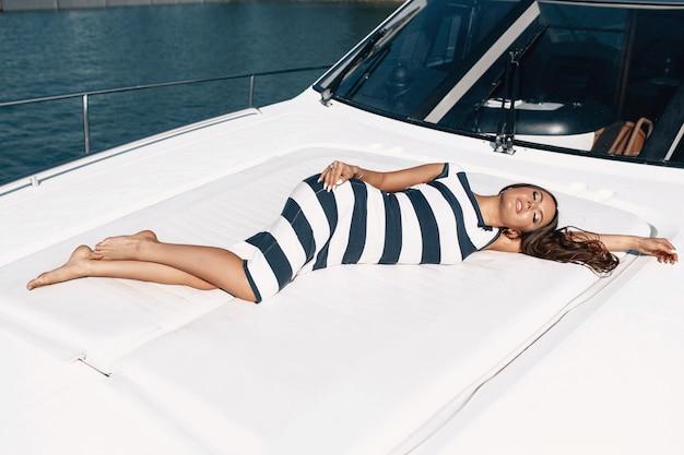Modelka w stylu kaukaskiej z makijażem w sukience w paski leży na pokładzie jachtu. podróżuj w gorących krajach. ścieśniać