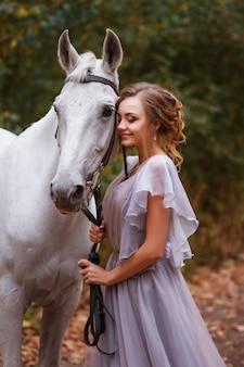 Modelka w sukience uśmiecha się i trzyma białego konia. tło zamazane, efekt artystyczny. zielone tło liściaste