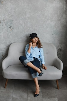 Modelka w wysokiej jakości, ubrana w buty na wysokim obcasie, kapelusz, niebieską koszulę i zwijane dżinsy. piękna młoda kobieta w modnym stroju siedzi na kanapie i pozuje we wnętrzu.