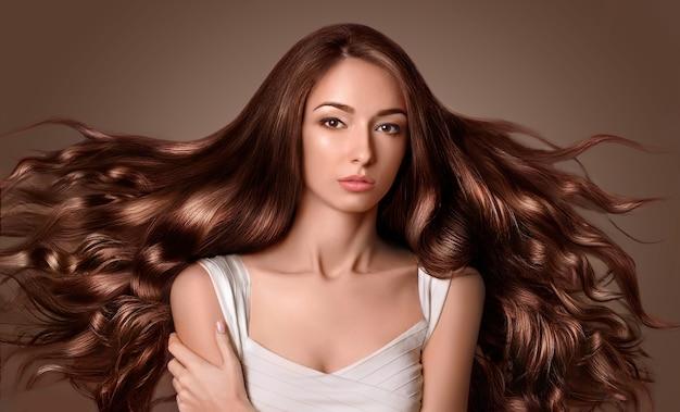 Modelka z długimi brązowymi włosami. fryzura waves curls. salon fryzjerski.