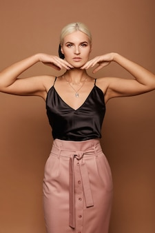 Modelka z doskonałym makijażem w czarnej bluzce i beżowej spódniczce, patrząc w kamerę i pozująca na beżowym tle