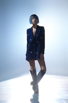 Modelka z fryzurą typu bob w niebieskiej kurtce z wystrojem z klejnotów oraz w szerokich wysokich butach na scenie pod kluczowym światłem