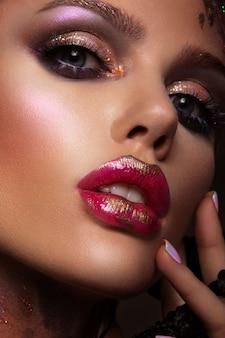 Modelka z jasnym makijażem i kolorowym brokatem