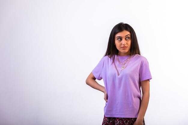 Modelka z rękami w talii patrząc na bok ze złością.