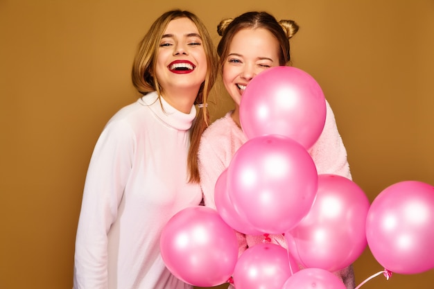 Modelki damskie z różowymi balonami na złotej ścianie