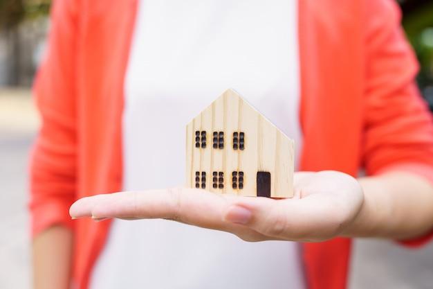 Modelowa modelka domu została umieszczona w the hands of asian business girl. pojęcie