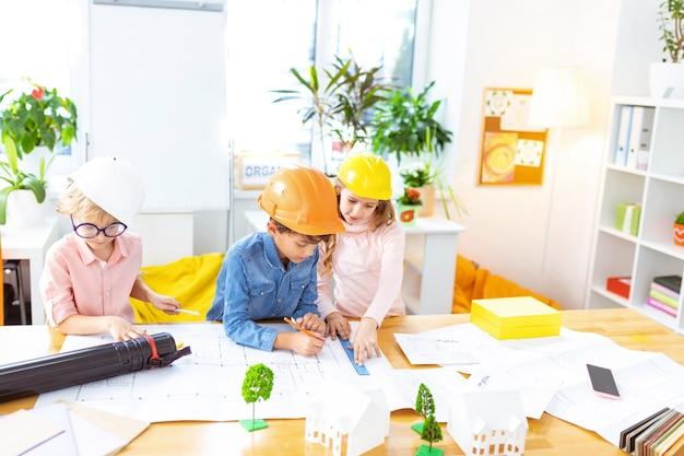 Modelowanie domu. dwóch chłopców i dziewczynka w kaskach uczących się w szkole podstawowej, studiujących modelowanie domów