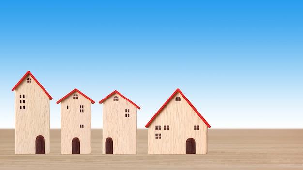 Modelowe drewniane domy na drewnianym biurku na niebieskim tle